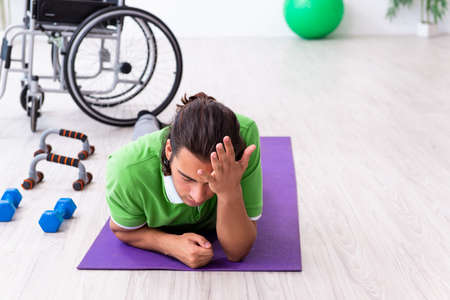 Young man in wheel-chair doing exercises indoors