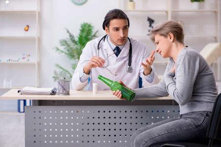 Female alcoholic visiting young male doctor Reklamní fotografie