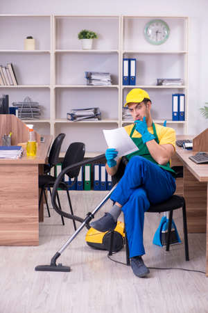 Young male contractor cleaning the office Stok Fotoğraf