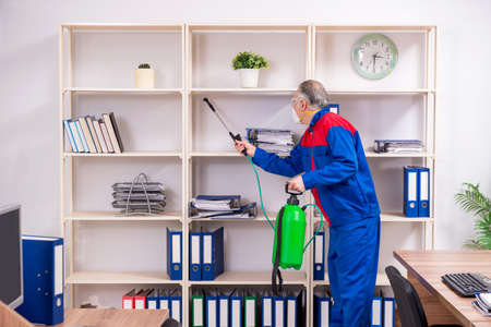 Old professional contractor doing pest control in the office Stock fotó
