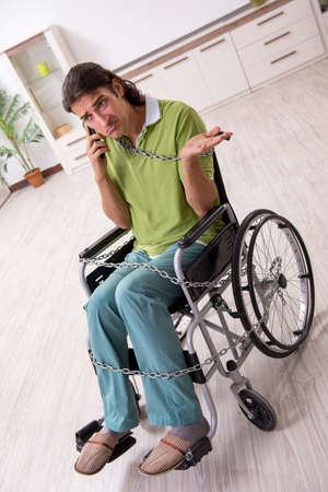 Young male invalid in wheel-chair suffering at home