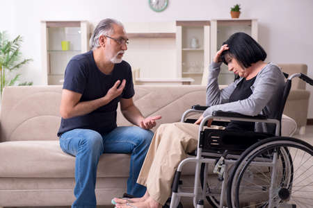 Old husband looking after disabled wife