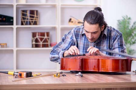 Young handsome repairman repairing cello Stockfoto