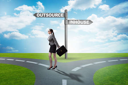 Businesswoman at crossroads deciding between outsourcing and inh