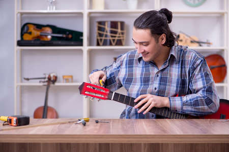 Young handsome repairman repairing guitar Stock Photo