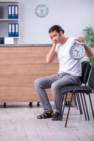 Young man at hospital reception desk