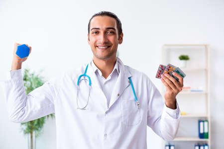 Junger männlicher Arzt im Sport- und Diätkonzept