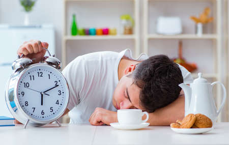Man with alarm clock falling asleep at breakfast 版權商用圖片