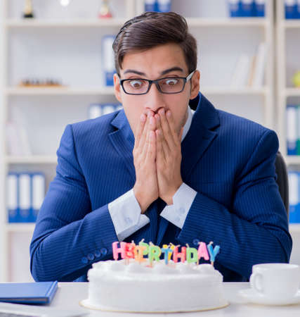 Young businessman celebrating birthday alone in office