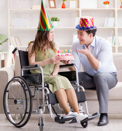 Young family celebrating birthday with disabled person Stok Fotoğraf