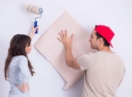 The young family doing renovation at home with new wallpaper Banco de Imagens