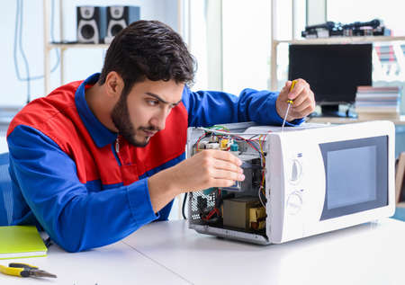 The young repairman fixing and repairing microwave oven