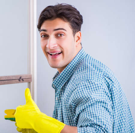 Young man cleaning mirror at home hotel