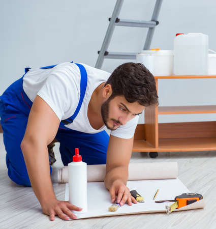 Repairman doing renovation repair in the house with paper wallpa
