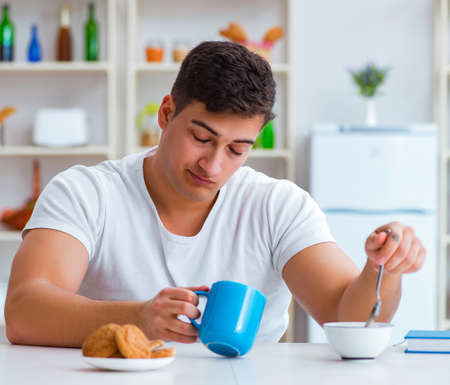 Man falling asleep during his breakfast after overtime work Stockfoto