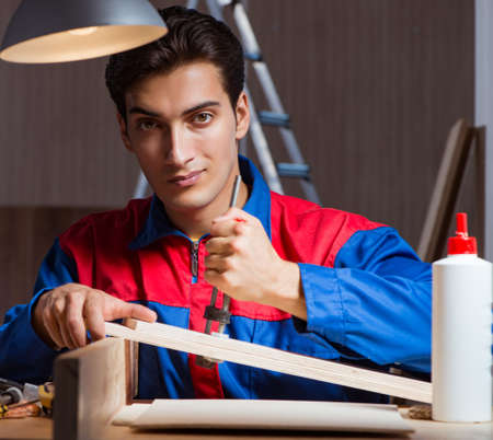Young man gluing wood pieces together in DIY concept Reklamní fotografie