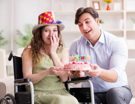 Young family celebrating birthday with disabled person Stock Photo