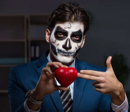The businessman with scary face mask working late in office Imagens