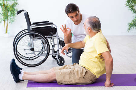 Old injured man doing exercises indoors