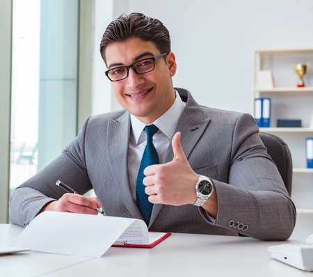 Businessman signing business documents in office