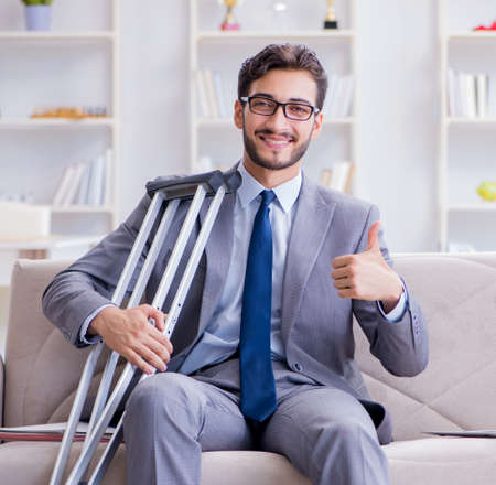 Businessman with crutches and broken leg at home working