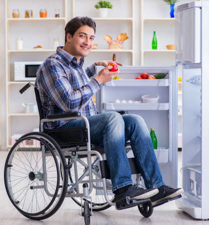 Young disabled injured man opening the fridge door Stock Photo