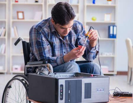 Disabled man on wheelchair repairing computer
