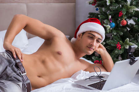 Sexy man in the bed wearing santa hat in christmas concept Banco de Imagens