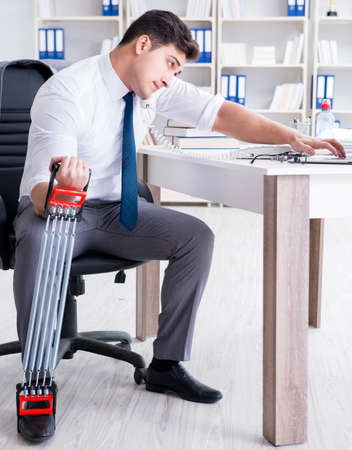 Young businessman exercising with elastic expander in office