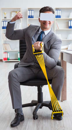 Businessman exercising with elastic expander wearing VR glasses 版權商用圖片