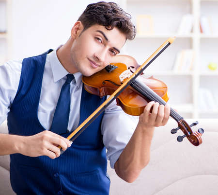 Young musician man practicing playing violin at home