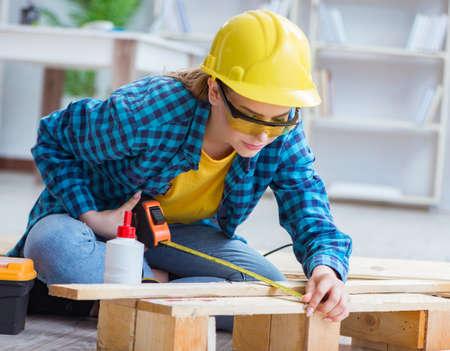 Female repairman carpenter cutting joining wooden planks doing r