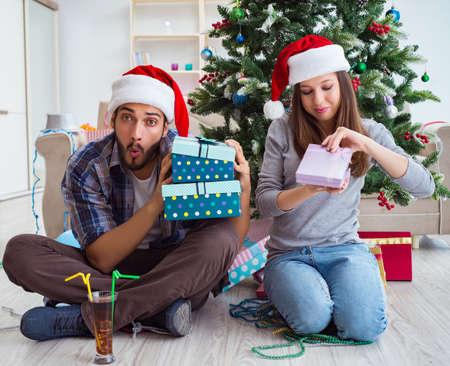 Girlfriend and boyfriend opening christmas gifts Banco de Imagens