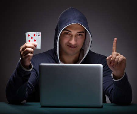 Young man wearing a hoodie sitting in front of a laptop computer Imagens