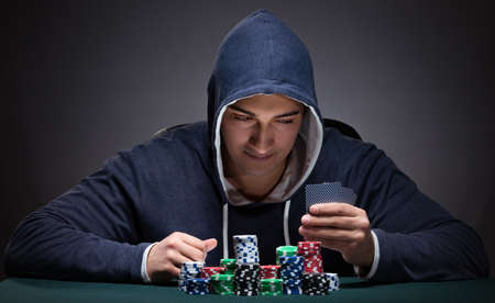 Young man wearing a hoodie with cards and chips gambling Фото со стока
