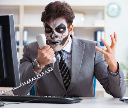 Businessmsn with scary face mask working in office Reklamní fotografie
