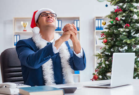 Businessman celebrating christmas holiday in the office Stockfoto