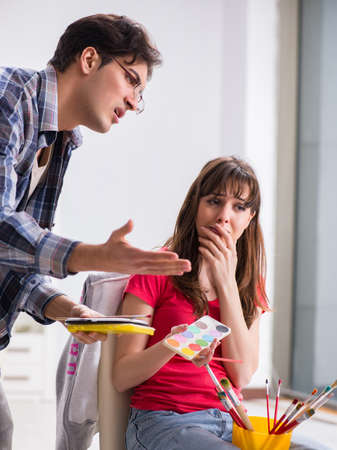 The artist coaching student in painting class in studio