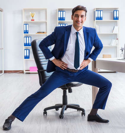 Young businessman doing sports stretching at workplace 版權商用圖片