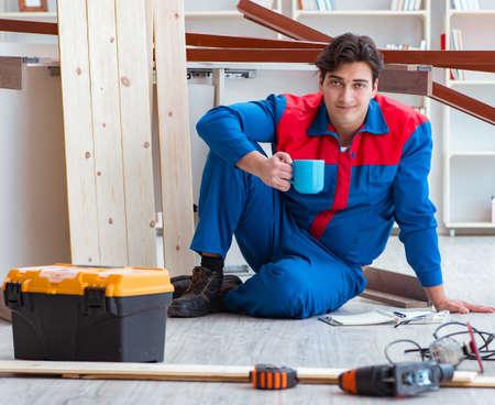 Jeune charpentier avec la planification d'écriture de cahier à la construction r