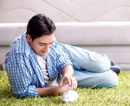 Young man playing with pet rabbit at home