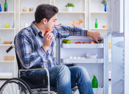 Young disabled injured man opening the fridge door Stok Fotoğraf