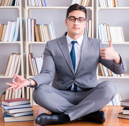 Businessman student in lotus position concentrating meditating Фото со стока