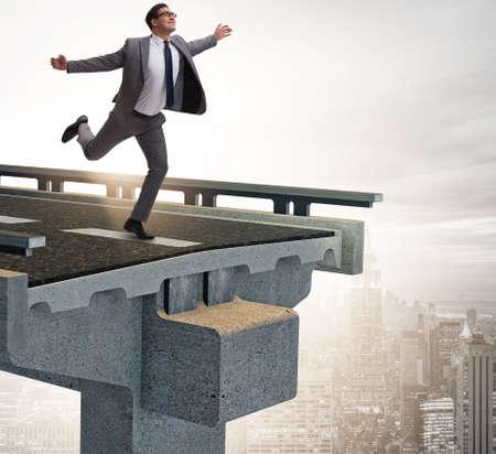 Businessman in uncertainty concept with broken bridge Imagens