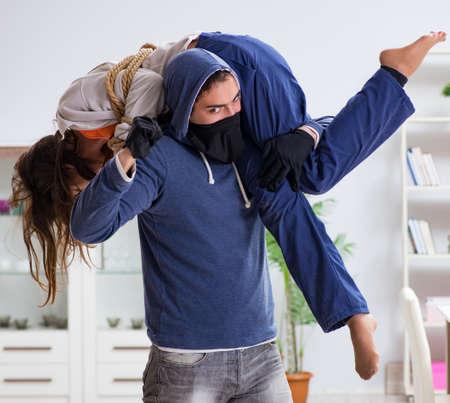Homme armé agressant une jeune femme à la maison