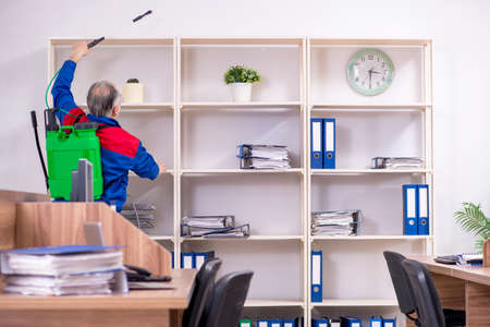 Old professional contractor doing pest control in the office Zdjęcie Seryjne