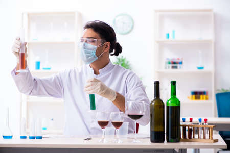Male chemist examining wine samples at lab Stok Fotoğraf