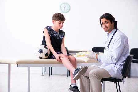 Boy football player visiting young doctor traumatologist