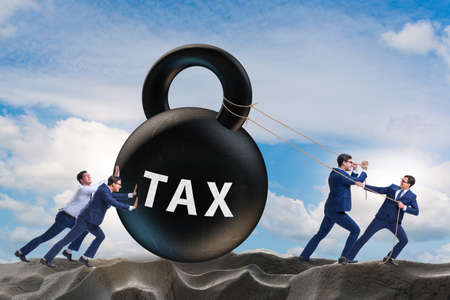 Businessman pulling kettle bell in tax concept
