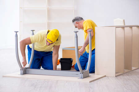 Two contractors carpenters working indoors Foto de archivo